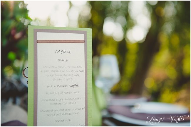 Green and Brown menu which is placed on the table. On the other side is a wooden heart with the table number on.