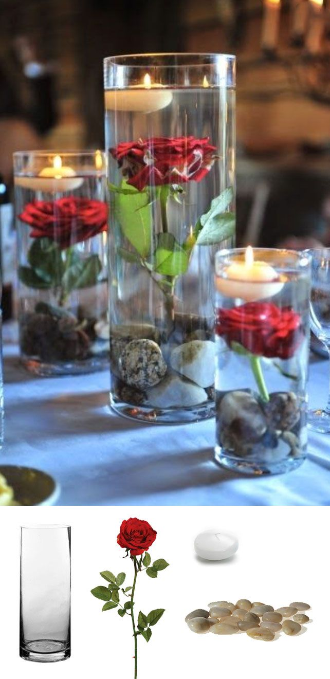 Beautiful and simple centerpiece to recreate for any wedding. All you need are cylinder vases, stones, faux roses, and floating candles. You can find all of these supplies at afloral.com! #diywedding