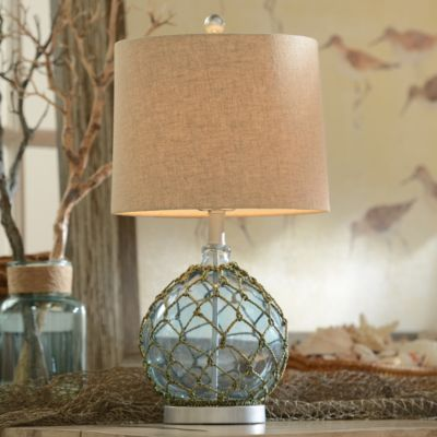 Combining the elements of a clear blue ocean and a handwoven fisherman's net, this glass lamp is a bounty of coastal style. #kirklands #FromCoasttoCoast