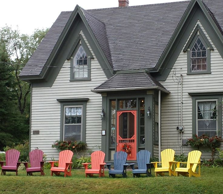 Colorful chairs against a gray house in Mahone Bay, Nova Scotia.