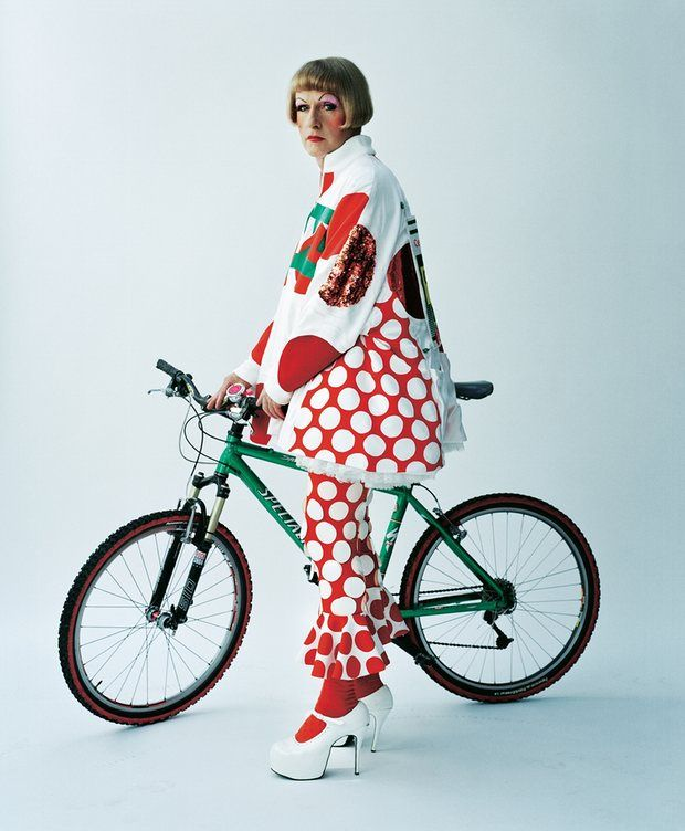 Grayson Perry in a spotty outfit with a bike