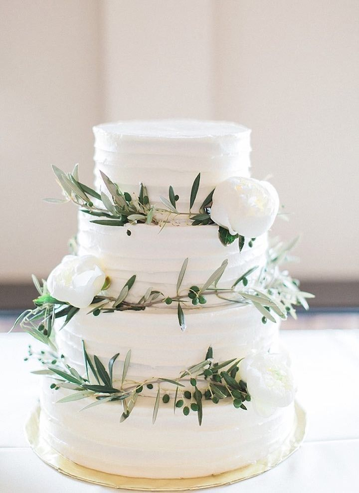 Photographer: Tracy Enoch Photograph; Add simple greens and white flowers to your white tiered wedding cake for an added rustic detail!