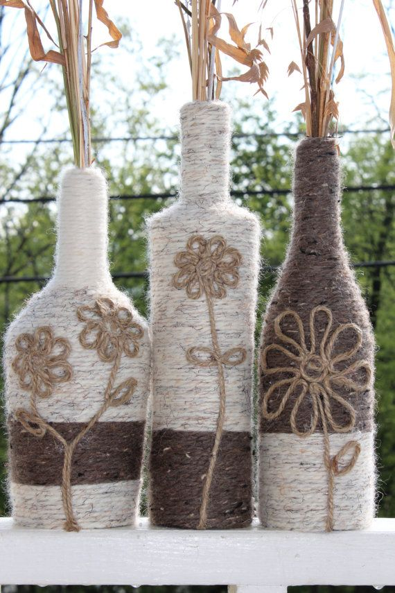 This set of 3 re-purposed wine bottles are wrapped with various colored yarns and twine. Each bottle has a detailed flower made from twine. They make
