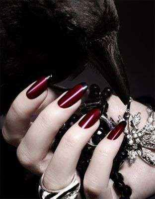 Crimson red nails with a black stripe.