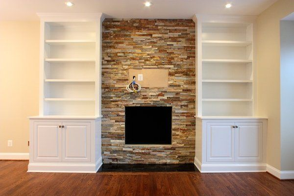 stone facades for fireplaces | Custom, handcrafted bookcases encase this stone fireplace facade.
