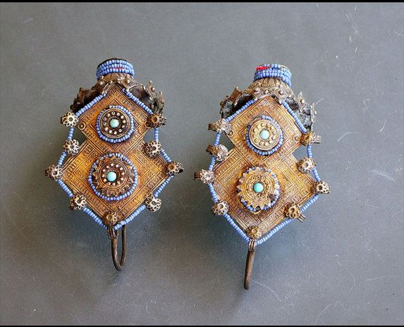 """Gilded Silver and blue Glass Ear Pendants from the Islamic people of the Katawaz basin along the border of Afghanistan/PakistanThese pendants were worn from the hair and headdress adjacent to the ears, being too heavy to be suspended from the ears. They comprise a """"basket"""" from which a """"flowering tree"""" grows and are fabricated from embossed silver gilt plaques attached to the silver base and trimmed with dozens of blue glass beads secured by fine wire."""