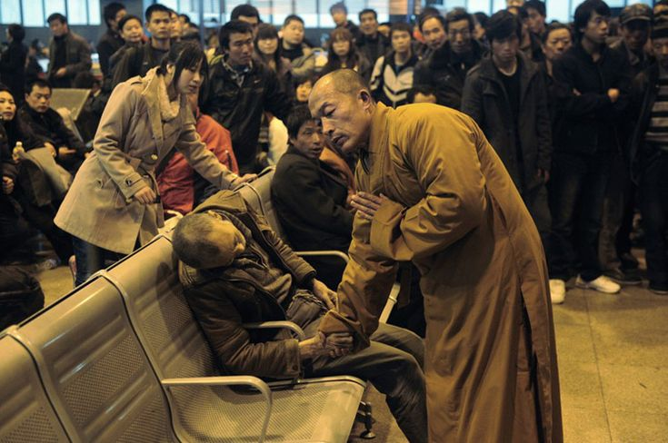 Monk prays for an elderly man who had died suddenly while waiting for a train in Shanxi Taiyuan, China.
