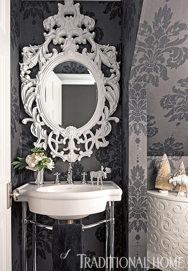 An ornate white mirror contrasts with the gray wallpaper behind it and dazzles above the bathroom sink. - Photo: John Granen / Design: Kristi Spouse