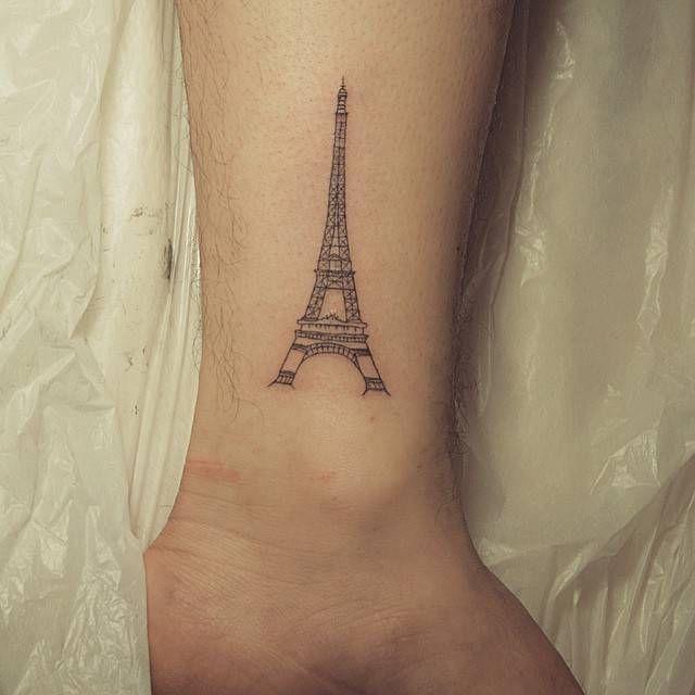 Fine line style eiffel tower tattoo on the ankle. Tattoo artist: Muha