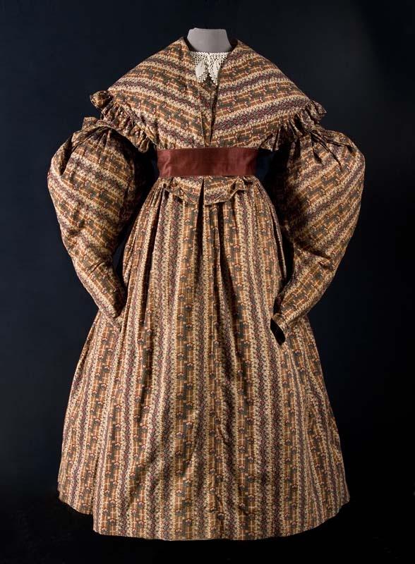 Printed cotton dress, dated 1835-1840, Fries Museum collection: T09606A. Site in Dutch. Biedermeier jurk van bedrukt katoen met schapenboutmouwen, bruin met rood-groen gebloemd banen en bijpassende pelerine kraag met ruche (B) Vervaardiger: onbekend Soort object: jurk Vervaardigingsdatum: 1835 - 1840 Afmeting: hoogte: 127.0 cm, taille: 62.0 cm, zoomwijdte: 280.0 cm, mouwlengte: 77.0 cm