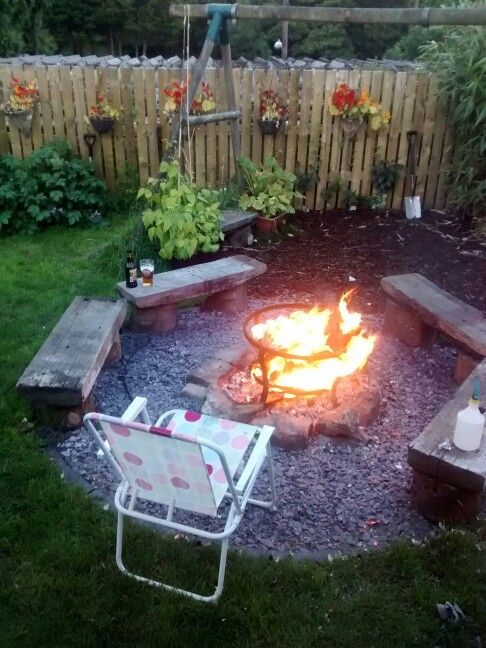 Homemade fire pit. Made from upcycled fire bowl sunk into ground. An unused collapsed wall provided the fire surround. The circle made out of bricks unfilled with slate chippings. Benches made from old railway sleepers and tree stumps.
