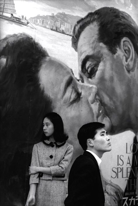 Henri Cartier-Bresson - Makes your eye move around the picture - Tokyo 1965 The clash of cultures - Japanese faces in western garb against the American movie poster backdrop... the public poster affection and the real life lack of warmth and relationship...