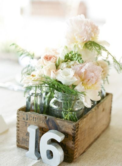 Flowers in glass bottles in wooden boxes
