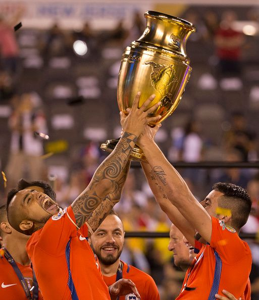 #COPA2016 #COPA100 Arturo Vidal of Chile and Mauricio Isla hold the Copa America Centenario Trophy following the championship match between Argentina and Chile at...