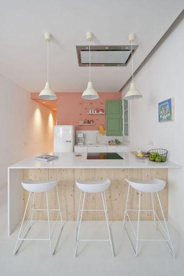 Cette cuisine avec bar s'organise autour d'un comptoir sur mesure sous lequel on peut ranger les tabourets hauts pour gagner de l'espace. L'association du blanc et du bois sied à merveille à cette cuisine vintage ouverte, dont le mur principal a été peint en rose saumon. On retient l'idée du sol blanc dans toute la « zone repas », facile à obtenir avec une peinture pour sol ou un revêtement vinylique.
