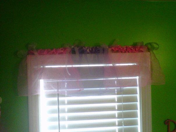 Used 3 tutus from dollar store. tacked them above window pane and tied sheer ribbon bows between each tutu....easy window treatment for a little girls bathroom.