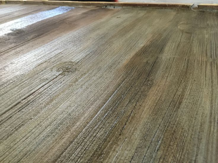Stained concrete floors that look like barn wood. To get the color you must stain over a micro-topping. I used a mixture of three parts water to one part driftwood acid stain. Let dry. Then mix one part water to one part gray water-based stain. Brush on lightly and let it dry.