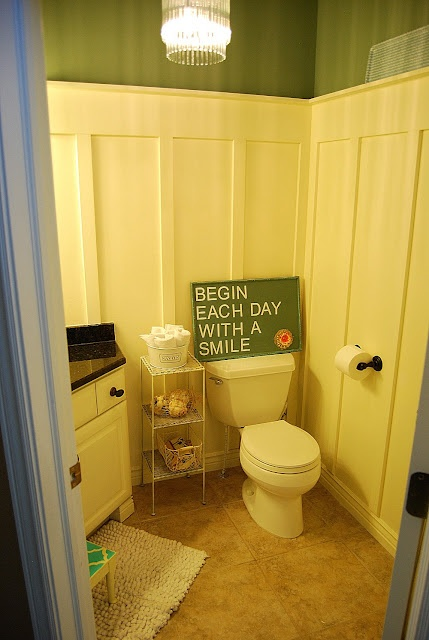 Board and Battenc guest bathroom! I love the green paint and the wood detailing!