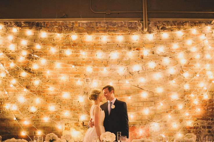 Cool use of lights for wedding background! this is so simple and cool to put on the side of the barn maybe. Would be pretty at dusk