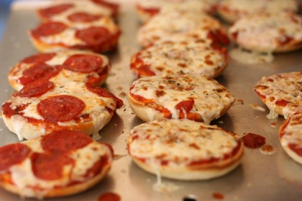 Pizza Bagels bagels tomato sauce shredded mozzarella cheese desired toppings Heat oven to 350 F. Place bagels on an ungreased baking sheet, cut side up. Spread a thin layer of tomato sauce over bagels, then top with cheese and desired toppings. Bake for 8-10 minutes, or until heated through. Broil for 2-3 minutes, or until cheese is spotty brown.