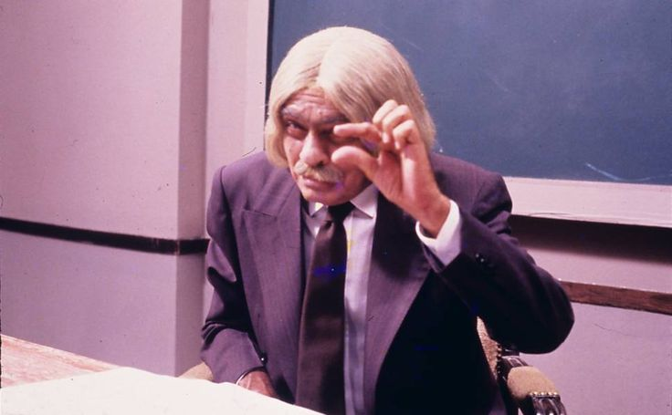 """Chico Anysio como o personagem Professor Raimundo, do programa """"Escolinha do Professor Raimundo"""", faz o gesto que acompanha o bordão """"E o salário, ó..."""""""
