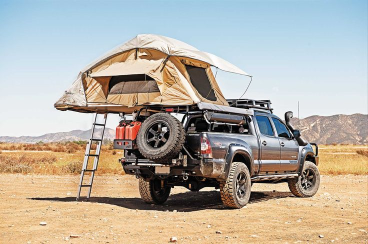 The All Pro-Off Road Expedition Series Pack Rack bed rack helps create organized storage space over the truck bed without compromising hauling capacity. A bevy of gear is attached to it, including an ARB Series III Simpson Roof Top Tent, ARB Awning 2000, and a Road Shower.