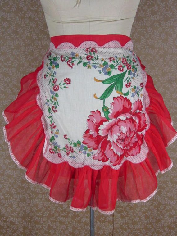 This is a genuine vintage red cotton handkerchief apron from the 1950s. The hankie is white cotton with a large red rose and red dots at the border. This is bordered with a wide solid red ruffle with white lace at the edge, waistband and ties. Super cute AND its not a small apron;