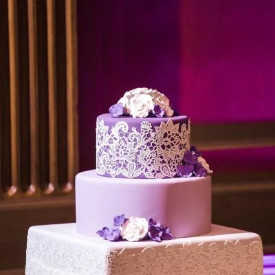 Three teir wedding cake with different shades of lavender fondant and intricate white designs with purple and white flowers scatterd   Genevieve Hansen Photography     villasiena.cc