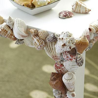Decorate a table with seashells! Conjure a tropical island on your porch or patio. All you need is a hot glue gun to attach shells onto a table for a beachy look.