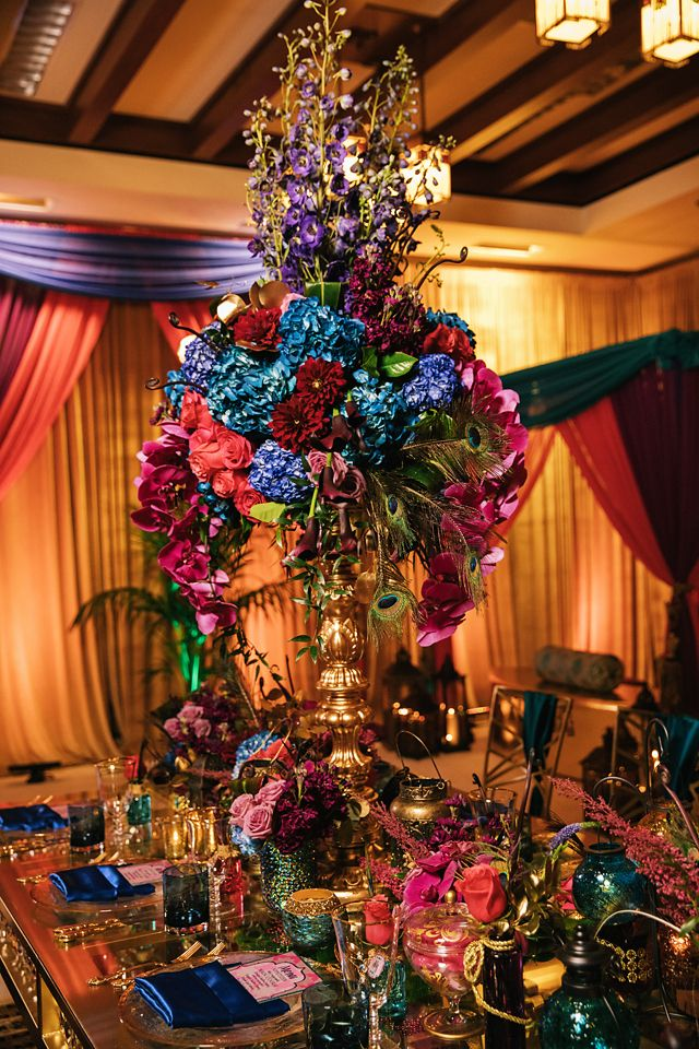 Princess Jasmine inspired reception setup with bright florals and bold colors