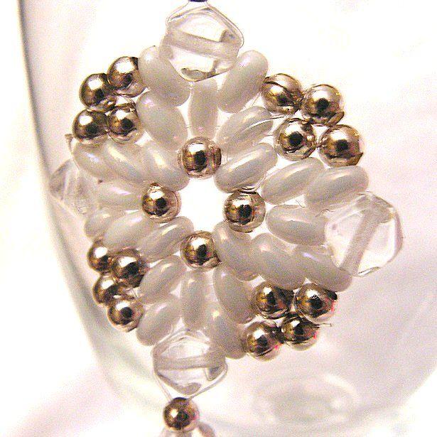 Náušnice z bílých twin korálků a drobných stříbrných korálků. Čtverec 3x3 cm je zavěšen nakoso a má malý přívěsek. Použila jsem afroháčky.