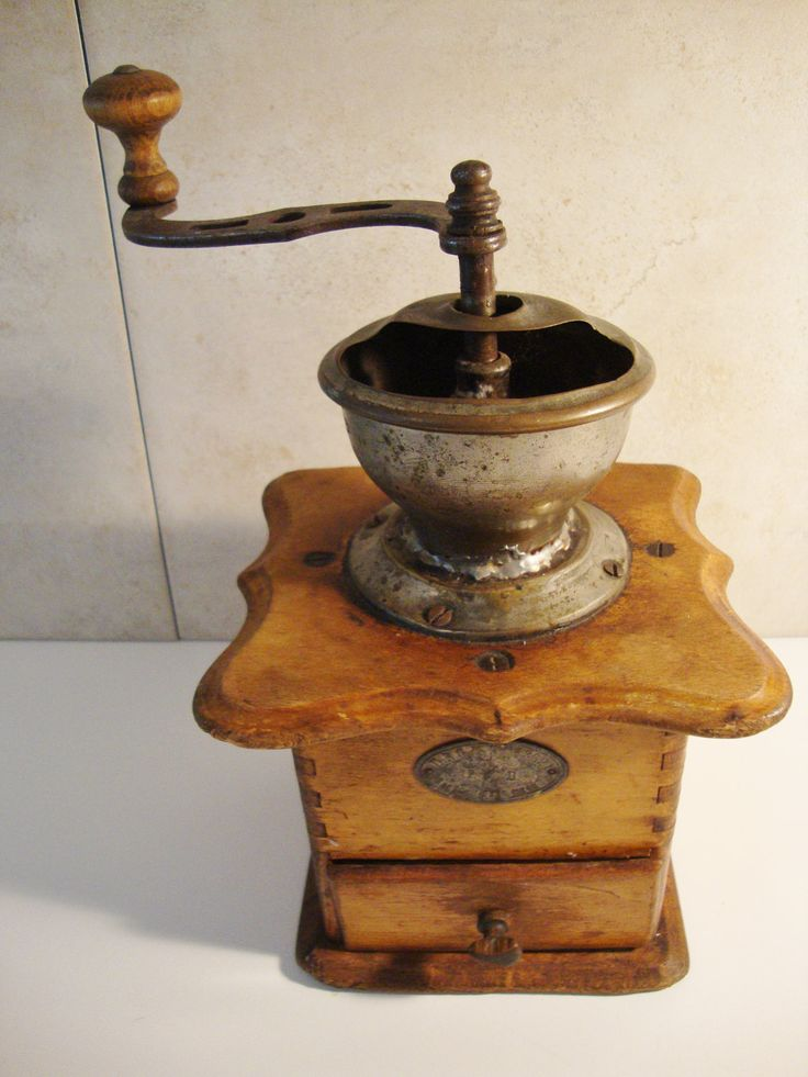 """This is a rustic coffee grinder purchased in an antique store in Germany in the late 1960's. It is primitive but well made with dovetail joints. It measures 10"""" at the highest point and the wooden part is 5"""" tall and 6"""" in diameter"""