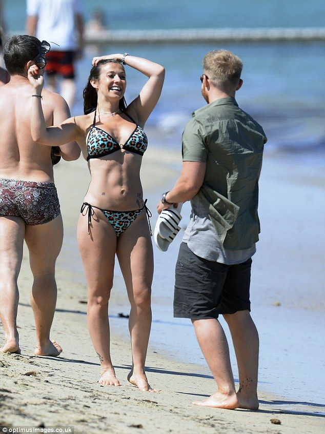 Loving life: Kym had the giggles as her man kept her entertained while on the beach