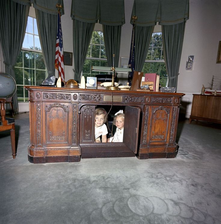 ST-C221-2-63. Caroline Kennedy and Cousin Kerry Kennedy Sit Under Desk in Oval Office - John F. Kennedy Presidential Library & Museum