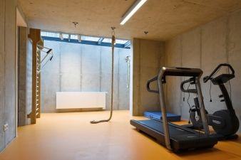 In the basement, a gym receives sunlight through a ground-level skylight