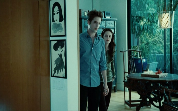 "Edward takes Bella home to meet the Cullen family. We see the front of the house when they pull up in Edward's Volvo; the entry area; the kitchen, where the Cullens cook Bella an Italiano meal to welcome her; two sets of stairs; and Edward's room. One of the stairs has graduation joke art on the wall (""We matriculate a lot"") and the other has a cross, described in the book, that was made by Carlisle's father in the 1600′s."