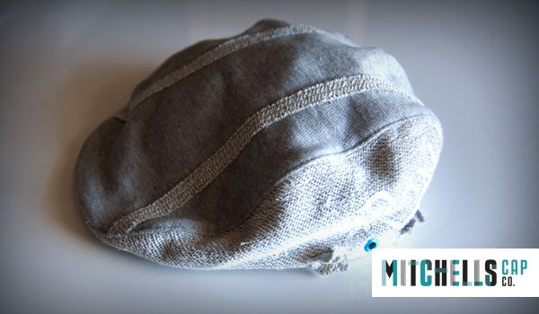 Mens Custom Winter Wholesale Hats : Mens Cheese Cutter hat in a wool and acrylic fabric paired with eyelet embellishments. Greys and browns, rough and smooth fabrics. Rustic and comforting.