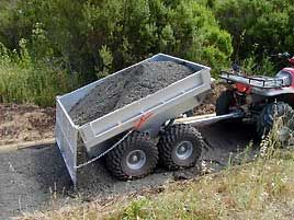 Photo of an ATV pulling a self-dumping trailer.