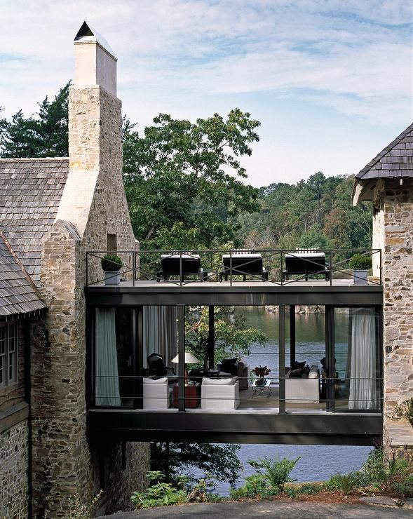 lake house with stone exterior and glass skyway white slipcovered sofa and chair brass - Lake House Design Ideas