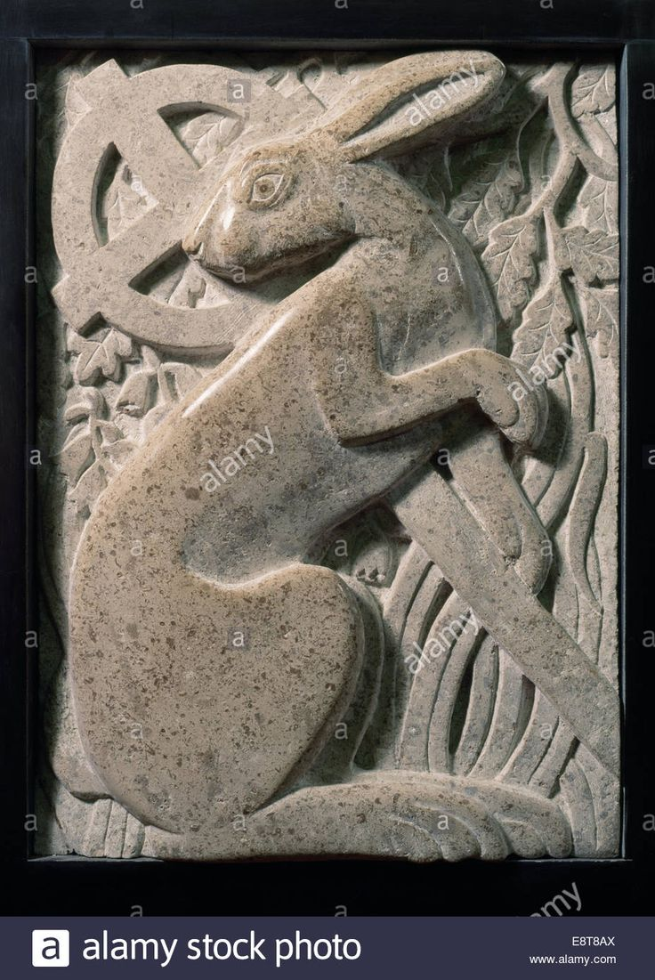 Modern stone carving of a hare with Celtic cross & oak leaves inside St Melangell's church, Powys: legend of St Melangell & hare Stock Photo