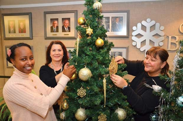 Christmas spirit: From left, City of Burnaby planning department employees Leah Libsekal, Donna Iacobellis and Lina Johannson help raise money for the Marguerite Dixon Transition Society every year. In all, about 20 employees help raise funds.