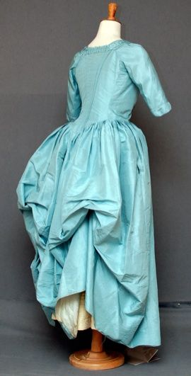 Polonaise Gown  c 1770-80  an open gown of mid blue tafetta silk, the front robings applied with a vandyked edged ribbon caught into tiny box pleats, short sleeves with added slightly pointed elbow edge, the back with fine tucks curving into the back waist, fine pleating to skirt, the fabric , the skirts sides with slits (for pocket access), the silk with yellow selvedges, the bodice lined with fine linen and with two linen tapes to skirt (to puff into a polonaise)