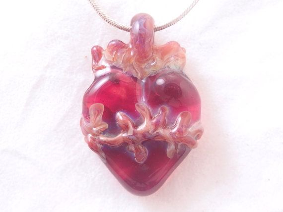 This one of a kind creation is going to be your new favorite piece of jewelry. A blazing transparent dark red Sacred Heart surrounded by black brown thorns. This meticulously sculpted borosilicate glass pendant is created without molds and is a one of a kind work. Commitment to craftsmanship is evident in attention to detail and quality of design. All glassworks are properly kiln annealed for lasting strength and durability.  Item Specifications  Pendant is 1 3/4 inches in length and 1 1/8…