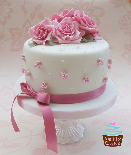 A cake designed for a lady with a love of roses for her 50th Birthday celebration.  Handmade pale pink sugar roses on the top of the cake with sugar rose buds around the sides.