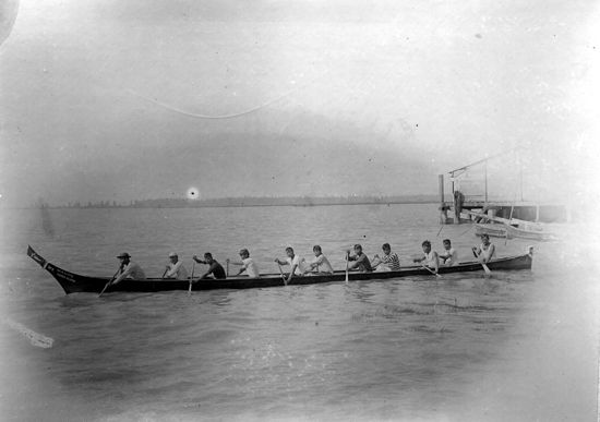 "11 First Nations men paddling long canoe on river (Strait of Georgia), ""Sea Lion No. 3 Kuper Island"" on bow"