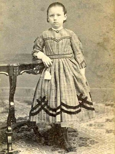 Young lady in plaid dress with narrow trim at bottom of bodice yoke, top and bottom of sleves and top and bottom of waistband.  AND wider trim on skirt.  Lovely accessories.