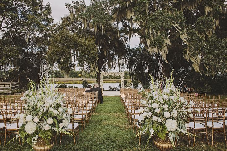 Glamorous Outdoor Ceremony with floral arbor and gold chivari chairs at Magnolia Plantation