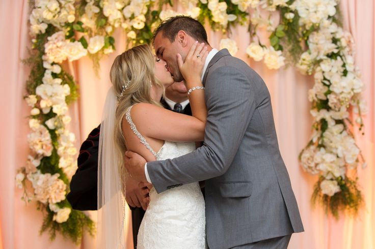 Bride and grooms first kiss in front of a floral backdrop at The Cocoa Room