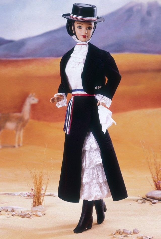 Chilean Barbie doll wears a charming costume based on the clothing of the huaso, or Chilean cowboy, which is worn for roundups and rodeos. Her bolero jacket is worn over a traditional dress with ruffles on the top and a black skirt on the bottom. Her costume sports a hat and sash banded in red, blue and white, the colors on the Chilean flag.
