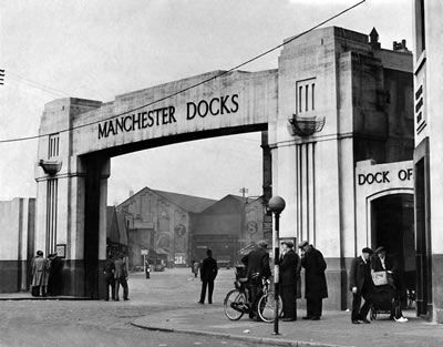 A few groups of men stand chatting at the gate of a deserted Manchester dock, May 1951 #Vintage #Classic #Old #Retro #Historic #OldFashioned #Manchester #MCR #NorthWest #photos #photographs #pictures #images #prints